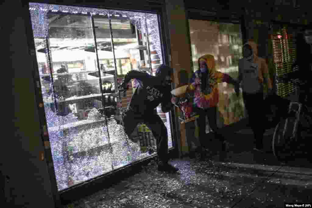Люди вистрибують із магазину товарів для курців через розбиту вітрину. Незважаючи на епідемію коронавірусу по усьому місту проходять акції протесту через смерть Джорджа Флойда. Нью-Йорк. 31 травня 2020 року (Фото AP/Wong Maye-E)