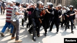 Police detain a supporter of ousted President Muhammad Morsi during clashes in central Cairo on August 13.