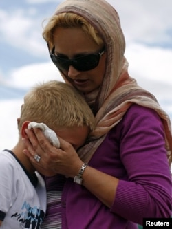 A Bosnian Muslim child is comforted as he cries during a mass funeral for victims killed during the 1992-95 war.
