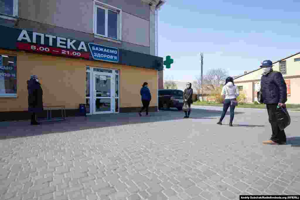 """Locals keep their distance as they wait in line outside a pharmacy. One resident of Kalynivka said the town's elderly residents initially poked fun at people wearing face masks """"then, as the situation developed, everyone quickly adopted [the masks]."""""""