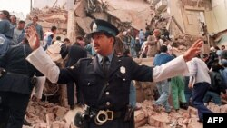 An Argentinian policeman prevents people from approaching the site where a powerful explosion destroyed the seven-story building housing the Jewish Mutual Association of Argentina in Buenos Aires in July 1994.