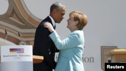 U.S. President Barack Obama (left) and German Chancellor Angela Merkel embrace after delivering remarks in the Bavarian village of Krun on June 7.