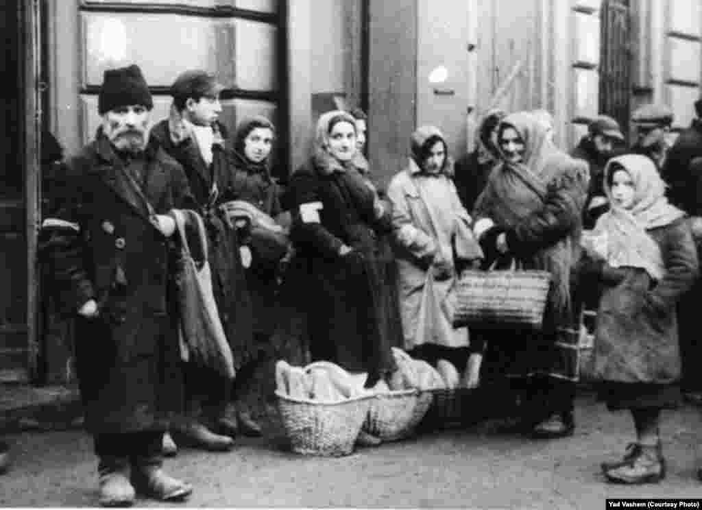 Jews stand by bread baskets on a ghetto street.