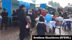 Граждане рядом с синими воздушными шарами на площади во время праздничных мероприятий по случаю Наурыза. Астана, 22 марта 2018 года.