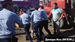 Сотрудники полиции уводят одну из участниц демонстрации торговцев у центрального рынка в городе Шымкенте. 30 июля 2018 года.