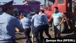 Полиция қызметкерлері орталық базар алдында сауда орнын бұзуға қарсылық танытқан әйелді әкетіп барады. Шымкент, 30 шілде 2018 жыл.