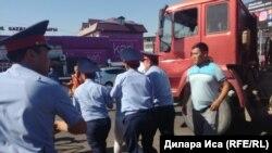 Сотрудники полиции уводят человека после его попытки воспрепятствовать сносу торговых точек на центральном рынке. Шымкент, 30 июля 2018 года.