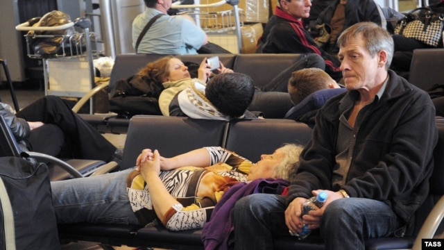 Passengers rest while waiting for a renewal of air traffic from Sheremerevo airport in Moscow on April 16.