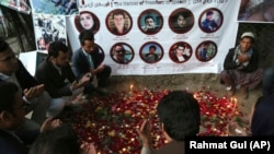 FILE: In May 2018, Afghans pray and light candles to pay tribute to Afghan journalists killed in a suicide attack in Kabul.