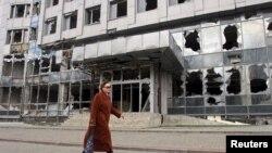 Женщина проходит рядом со зданием, поврежденным в ходе обстрелов. Донецк, 15 апреля 2015 года.
