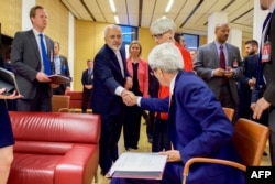 US Secretary of State John Kerry shakes hands with Iranian Foreign Minister Javad Zarif as he prepares to leave the Austria Center in Vienna, July 14, 2015