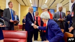 Государственный секретарь США Джон Керри (справа) пожимает руку министру иностранных дел Ирана Мохаммаду Джаваду Зарифу после окончания переговоров по ядерной программе. Вена, 14 июля 2015 года.
