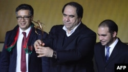 The president of Afghanistan's soccer federation, Karim Keramuddin (center), holds up the 2013 FIFA Fair Play Award in Zurich on January 13.
