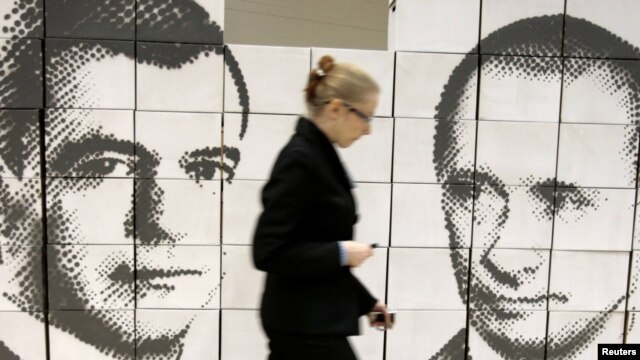 A woman walks by a panel made of cardboard boxes, displaying President Dmitry Medvedev (left) and Prime Minister Vladimir Putin in Rostov na Donu, 21Oct2010