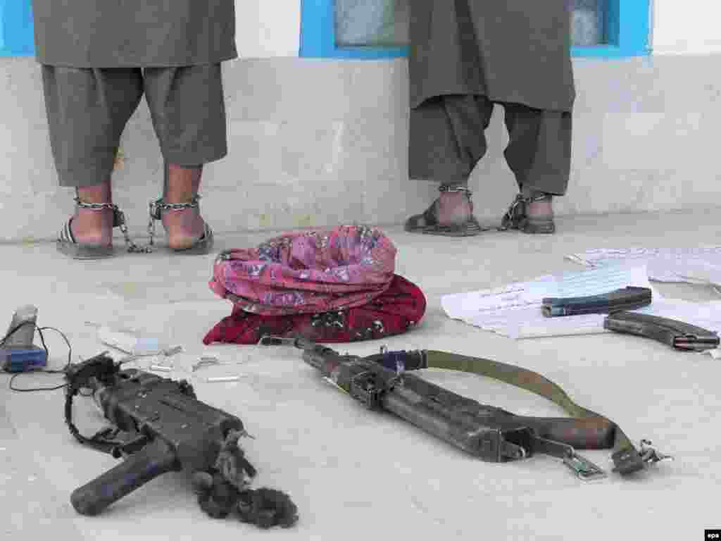 Afghan police show off two suspected militants to the media in Kandahar. The two were arrested during a security operation; arms and bomb-making materials were allegedly in their posession. Photo by Humayoun Shiab (epa)