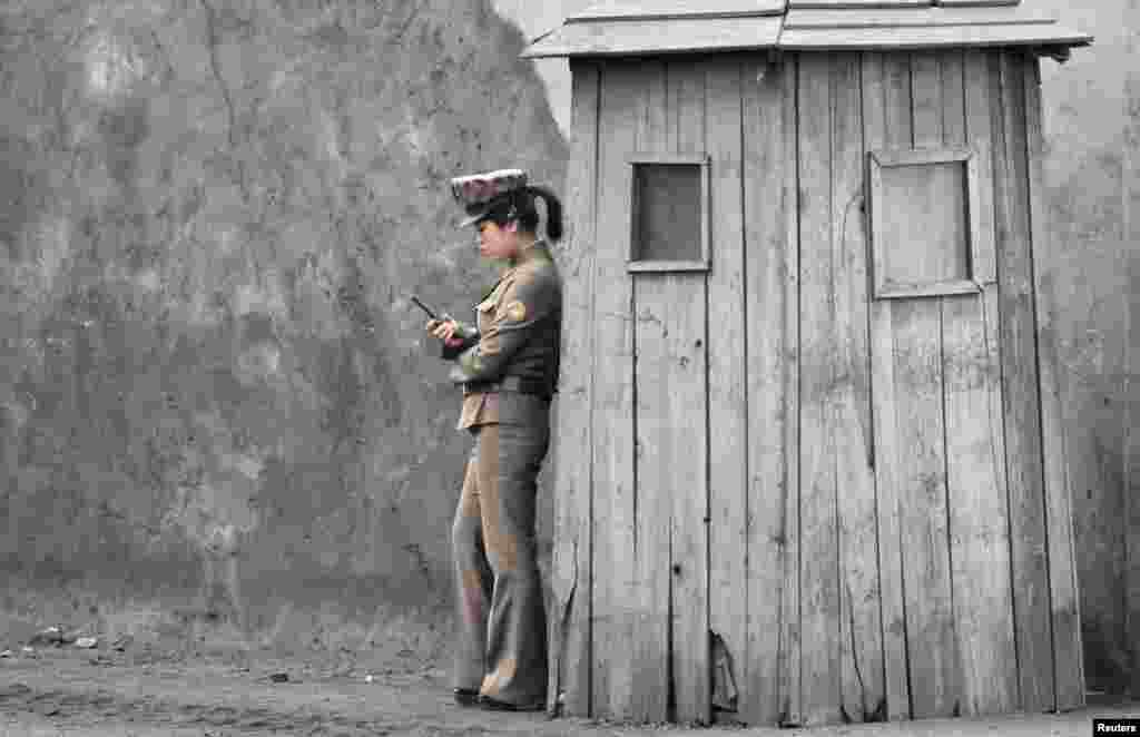 A female North Korean soldier uses her mobile phone next to a sentry on the banks of the Yalu River, near the town of Sinuiju, opposite the Chinese border city of Dandong. (Reuters/Jacky Chen)