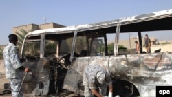 Iraqi police inspect a burnt bus at the site of a bomb attack in Baghdad on November 24.