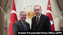 Turkish President Recep Tayyip Erdogan (R) shakes hands with U.S. Senator Lindsey Graham (L) as they pose for a photo at Presidential Complex in Ankara, January 18, 2019