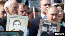 """Справа - президент России Владимир Путин несет портрет своего отца на марше """"Бессмертный полк"""". Москва, 9 мая 2015 года."""