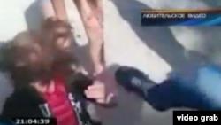 Құрбысын теуіп жатқан оқушы қыз. КТК телеарнасының YouTube парақшасындағы видеодан алынған сурет.