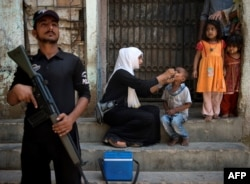 A Pakistani policeman stands guard as a health worker administers the polio vaccine to a child during a vaccination campaign in Karachi, Pakistan, in April. More than 80 polio vaccination team workers in Pakistan have been killed by Taliban militants since a massive polio eradication effort was launched in 2012.