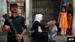 Derisa punëtorja shëndetësore e vaksinon fëmijën, në mbrojtje qëndron ushtari pakistanez