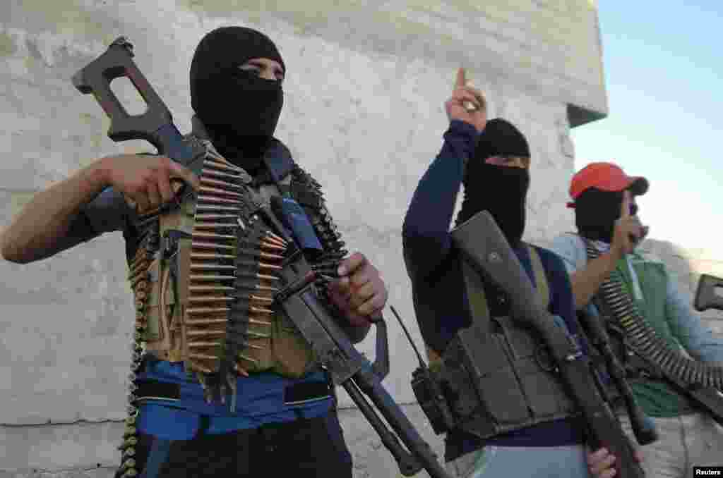 Masked Sunni gunmen pose with their weapons during a patrol outside the city of Falluja.