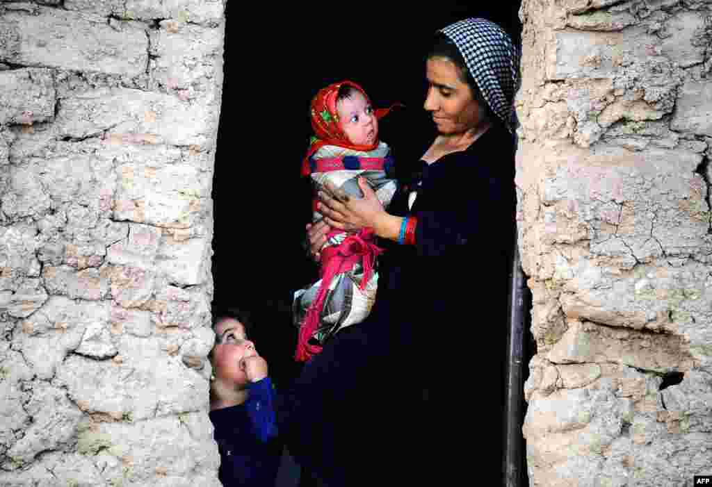 An internally displaced Afghan resident holds her child as she stands in the doorway of her temporary shelter on the outskirts of Herat Province. (AFP/Aref Karimi)