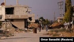 Дамаскіде қираған ғимараттың жанында кетіп бара жатқан адамдар. Сирия, 23 шілде 2017 жыл (Көрнекі сурет).