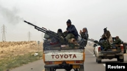 Libya -- A rebel fighter fires his anti-aircraft gun as he flees together with other rebel fighters from Ajdabiyah, outside Ajdabiyah on the road to Benghazi, 15Mar2011
