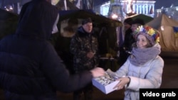 Sofia Marchenko hands out cookies in Kyiv.
