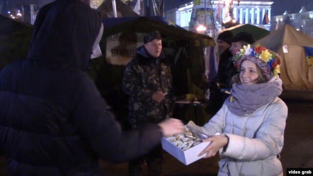 Student Sofia Marchenko hands out baked cookies for Euromaidan protesters in Kyiv last winter.