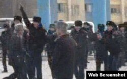 Полицейские стоят на центральной площади города Жанаозен. 16 декабря 2011 года. Скриншот с видеопртала Стан.кз.