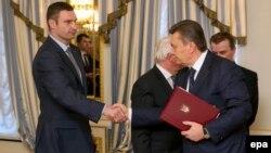 """Лидер партии """"УДАР"""" Виталий Кличко (слева) и президент Украины Виктор Янукович после подписания соглашения между властями и оппозицией. Киев, 21 февраля 2014 года."""