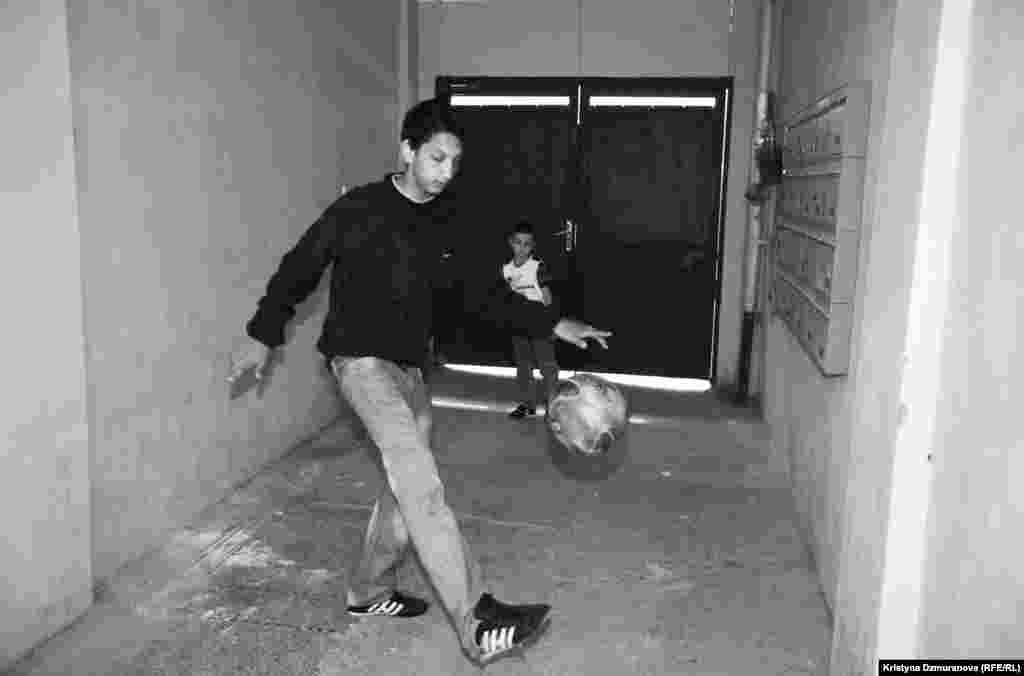 Emil Jr. and Rudolf play soccer in the entryway to their apartment building. Emil is a passionate soccer player and plays every day with friends from the neighborhood. He warms up by teaching Rudolf some tricks.