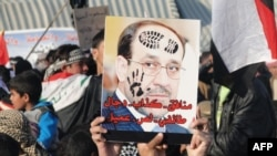 Iraqi Sunni protesters hold up a defaced portrait of Prime Minister Nuri al-Maliki in Ramadi on January 4.