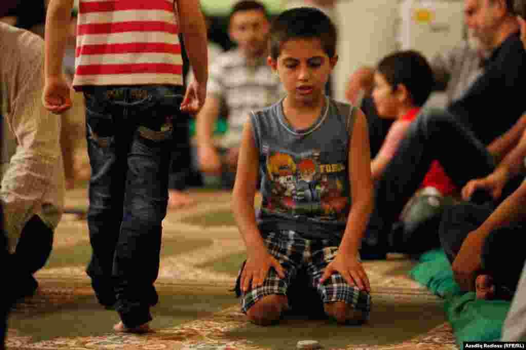 Напередодні свята Ураза-байрам віряни роблять благодійні приношення: продукти (в основному сухі солодощі) або гроші, еквівалентні вартості таких продуктів. Зібране йде малозабезпеченим, мандрівникам На фото – хлопчик на молитві в мечеті. Баку