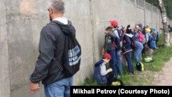Михаил Петровтың Псковтағы әскери бөлім дуалына соғысқа қарсы үндеген сурет салып тұрған сәті
