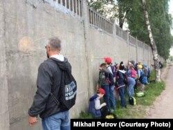 Физрук с воспитанниками раскрашивают забор военной части в Пскове.