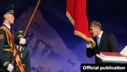 Almazbek Atambaev kisses the Kyrgyz flag during his presidential inauguration ceremony in Bishkek on December 1.