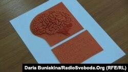 Майбутня сторінка із зображенням мозку та описом шрифтом Брайля