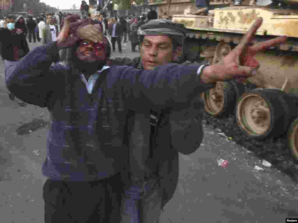 An injured antigovernment protester is helped during clashes on Tahrir Square.