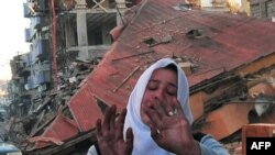 A woman cries in front a collapsed house after the October 23 earthquake in the Ercis province of Van, in Turkey.