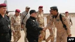 Премьер-министр Ирака Хайдер аль-Абади (в центре) здоровается с офицерами по прибытии в город Мосул. 9 июля 2017 года.