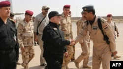 A handout picture released by the Iraqi premier's press office shows Prime Minister Haidar al-Abadi (center) shaking hands with army officers upon his arrival in Mosul on July 9.