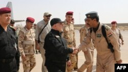 A handout picture released by the Iraqi prime minister's press office on July 9, 2017, shows Iraqi Prime Minister Haider al-Abadi (c) shaking hands with army officers upon his arrival in Mosul.