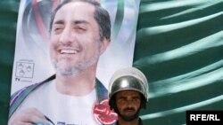 Owgan polisiýa işgäri prezidentlige kandidat Dr. Abdullahyň portretiniň öňünde, Kabul, 2009-njy ýylyň 29-njy iýuly.
