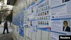 Парламент сайлауына түсіп жатқан кандидаттардың жарнамалары жанынан өтіп бара жатқан адам. Алматы, 11 қаңтар 2012 жыл. (Көрнекі сурет.)