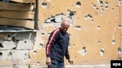 Чоловік біля пошкодженого обстрілами будинку, Донецьк, 19 травня 2015 року