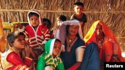 Hindu immigrant woman and children from Pakistan sit at a shelter in Rajasthan, India.